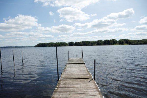 En brygga som går ut i en sjö en vacker sommardag. I bakgrunden syns en trädlinje på andra sidan sjön.