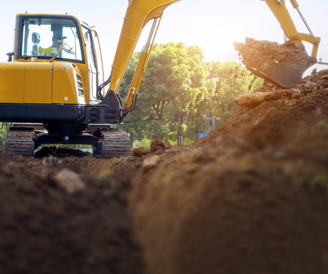 En gul grävmaskin gräver i marken och lägger massorna i en hög