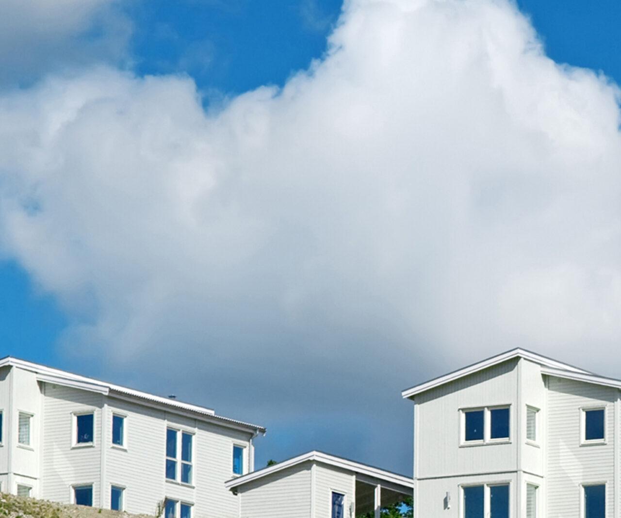 Nybyggda vita flerbostadshus mot en vacker blå himmel med moln