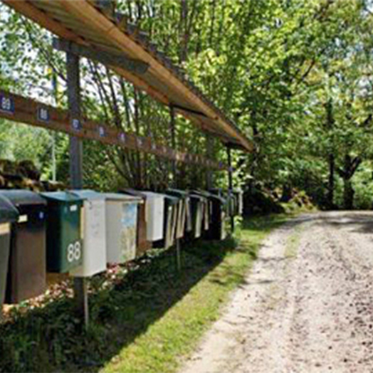 Postlådor på rad vid en grusväg med skog i bakgrunden
