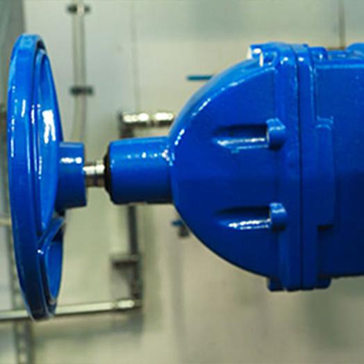 En blå maskindel med en vägg med vattenrör i bakgrunden
