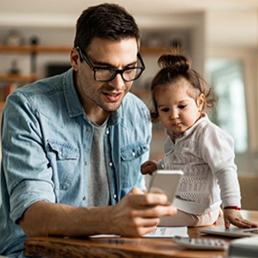 En man och ett spädbarn som sitter på bordet tittar på en mobiltelefon