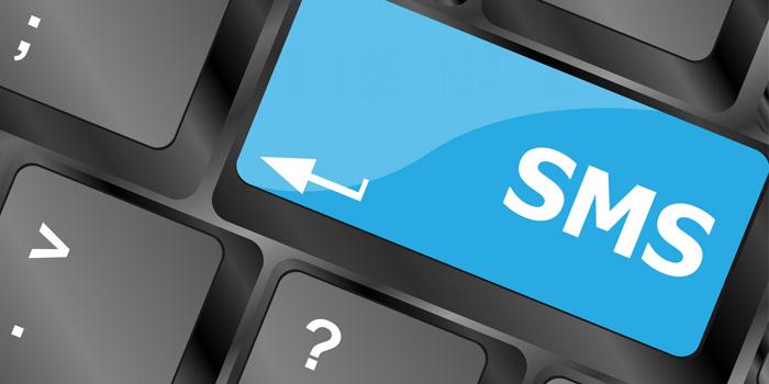 Närbild på tangentbord där enter-knappen är på med texten SMS