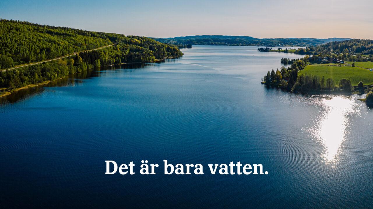 Vy över grönskande land och stilla vatten